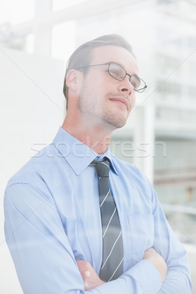 Thoughtful businessman standing with arms crossed Stock photo © wavebreak_media