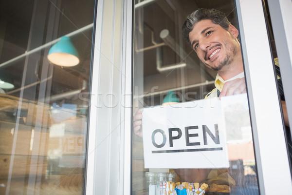 Smiling worker putting up open sign Stock photo © wavebreak_media