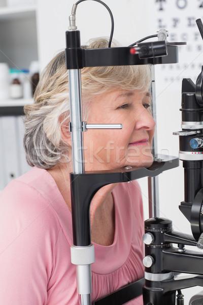 Senior patient looking into slit lamp Stock photo © wavebreak_media