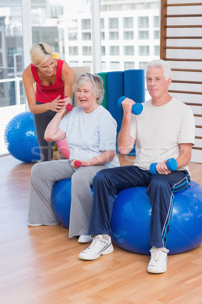 Trainer motivating senior couple in lifting dumbbells Stock photo © wavebreak_media