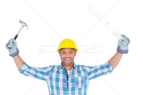 Smiling handyman holding hammer and level Stock photo © wavebreak_media