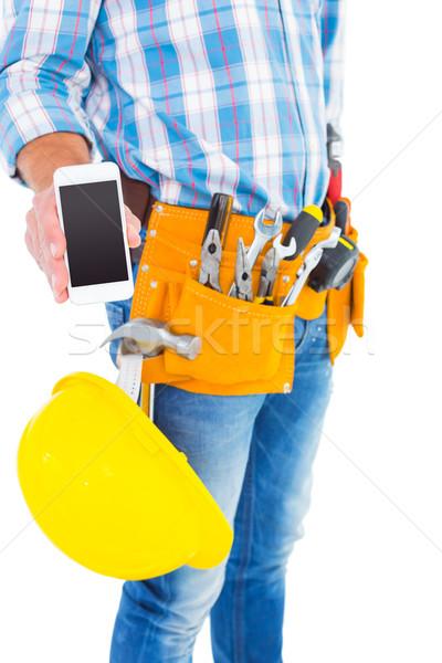 Midsection of handyman showing smartphone Stock photo © wavebreak_media