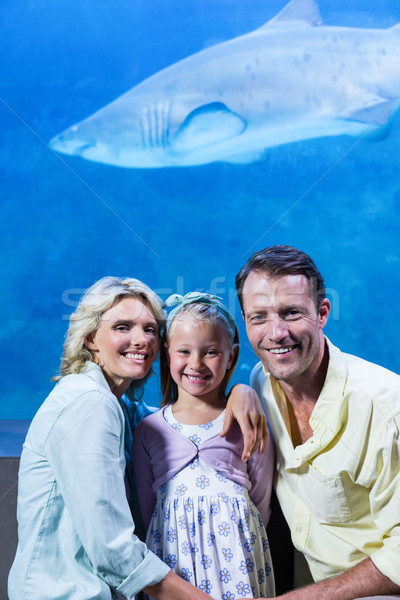 Happy family looking at camera beside the fish tank Stock photo © wavebreak_media
