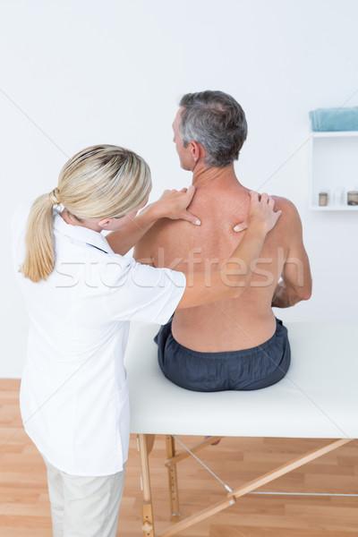 Doctor examining her patient back  Stock photo © wavebreak_media
