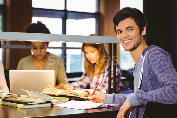 Student looking at camera with his classmates behind him Stock photo © wavebreak_media