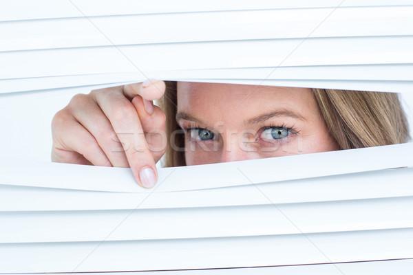 Woman peering through roller blind Stock photo © wavebreak_media