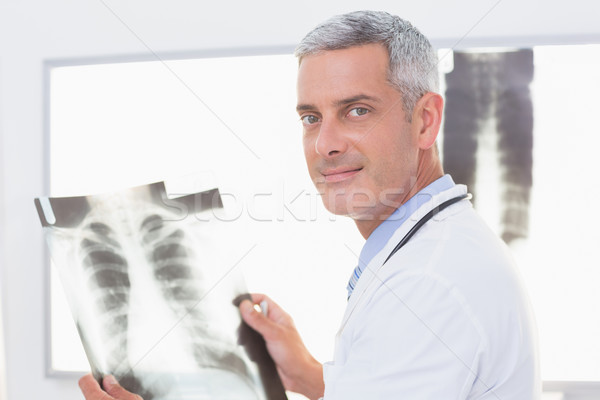 Smiling doctor looking at X-Rays  Stock photo © wavebreak_media