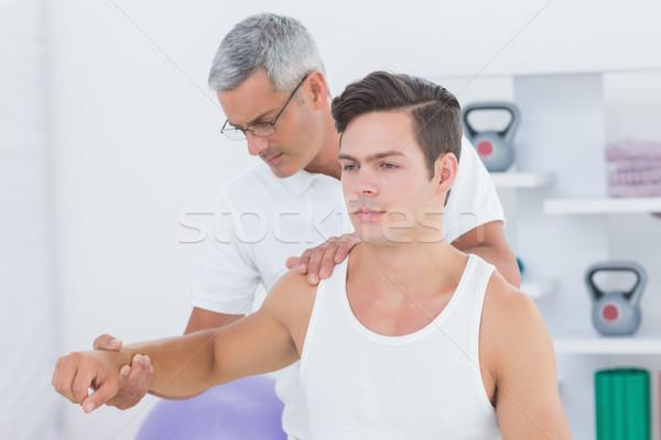 Médecin jeune homme bras médicaux bureau Photo stock © wavebreak_media