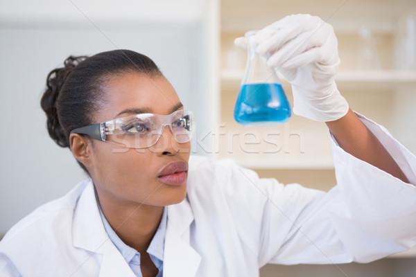 Scientist examining petri dish with blue fluid inside Stock photo © wavebreak_media