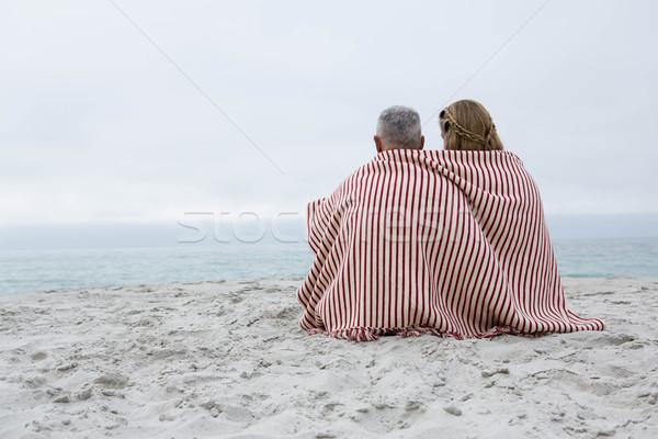 Happy couple sitting on the sand with blanket around them Stock photo © wavebreak_media