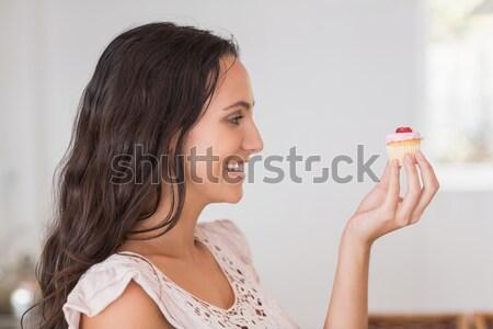 Beautiful brunette holding mini cupcake Stock photo © wavebreak_media