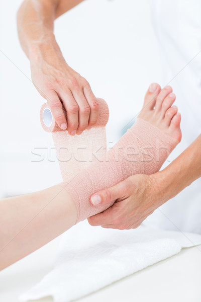 Doctor bandaging her patient ankle  Stock photo © wavebreak_media