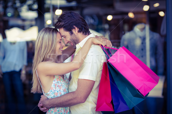 Smiling couple with shopping bags hugging closely Stock photo © wavebreak_media