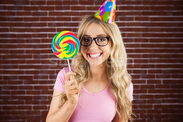 Portrait of a hipster with a party hat holding a lollipop Stock photo © wavebreak_media