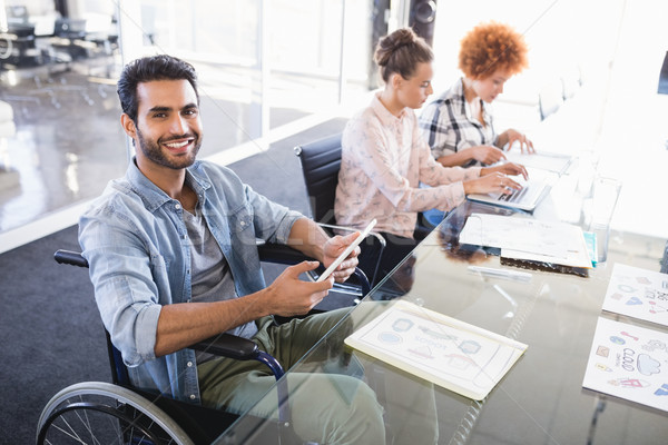 High angle portrait of smiling businessman using digital tablet while sitting on wheelchair Stock photo © wavebreak_media