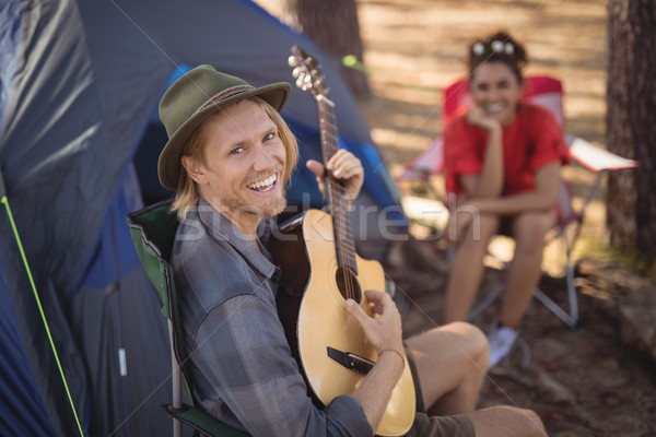 Portrait of smiling man playing guitar while his girlfriend sitting in background Stock photo © wavebreak_media