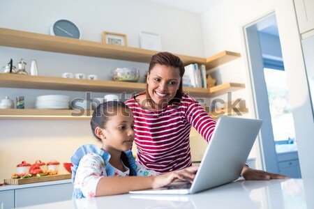 Happy family using laptop in kitchen worktop Stock photo © wavebreak_media