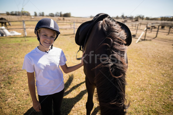 Smiling girl standing next to the brown horse in the ranch Stock photo © wavebreak_media