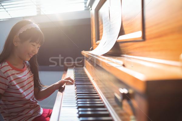 Smiling girl practicing piano in class Stock photo © wavebreak_media