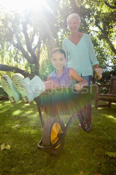 Smiling grandmother pushing granddaughter in wheelbarrow Stock photo © wavebreak_media