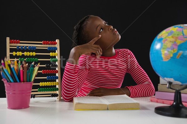 Schoolgirl reading book against black background Stock photo © wavebreak_media