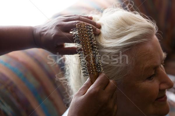 Cropped hands of doctor combing hair of female patient Stock photo © wavebreak_media