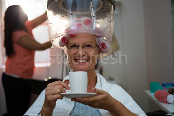 Portrait of senior woman having drink while sitting under hair steamer Stock photo © wavebreak_media