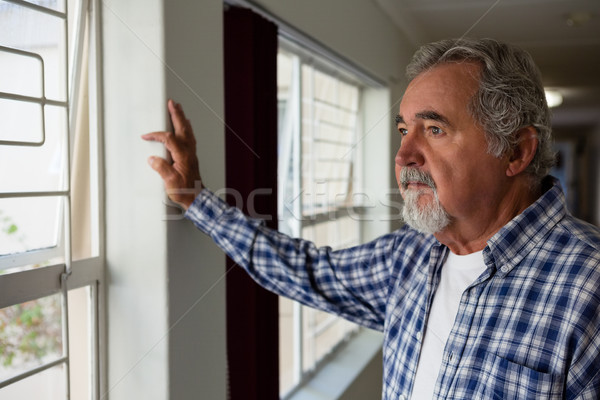 Thoughtful senior man looking through window at nursing home Stock photo © wavebreak_media