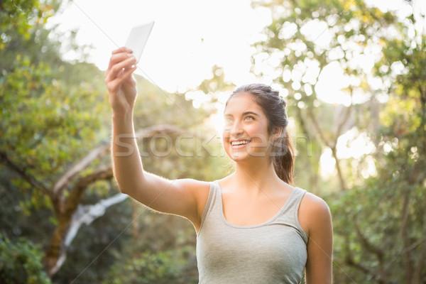 Smiling athletic brunette taking selfies Stock photo © wavebreak_media