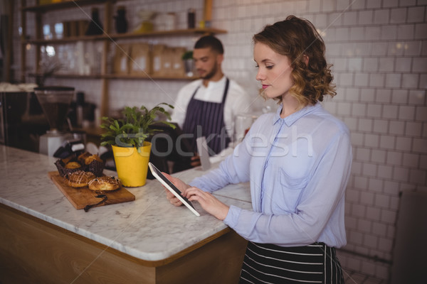 Young waitress using tablet computer while standing at counter Stock photo © wavebreak_media