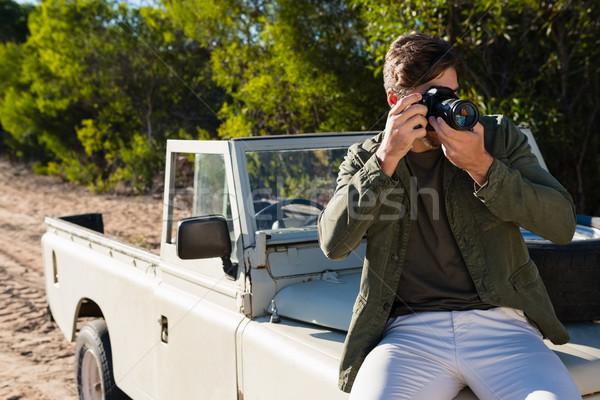 Man photographing while sitting on vehicle hood Stock photo © wavebreak_media