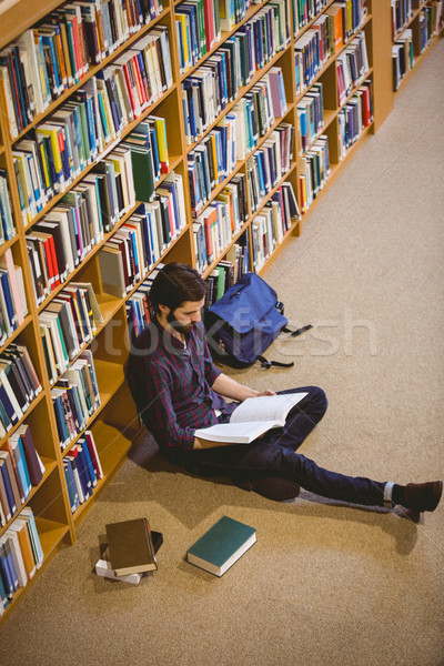 Student reading book in library on floor Stock photo © wavebreak_media