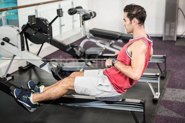 Muskularny człowiek wioślarstwo maszyny siłowni szkolenia Zdjęcia stock © wavebreak_media