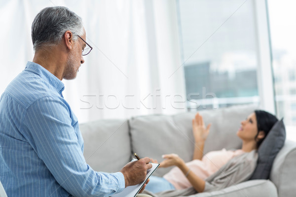 Doctor writing on notepad while consulting pregnant woman Stock photo © wavebreak_media