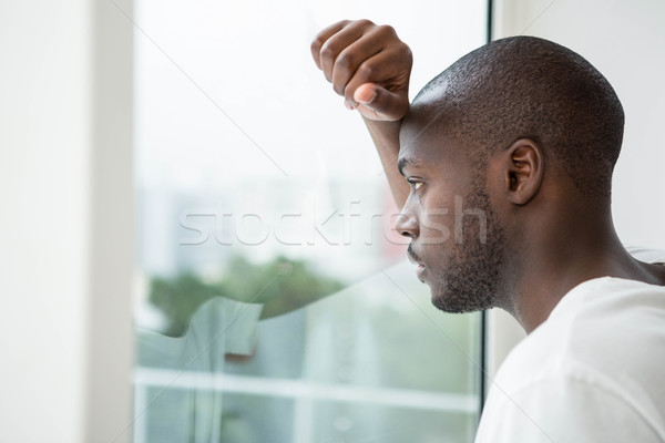 Homem olhando fora janela quarto Foto stock © wavebreak_media
