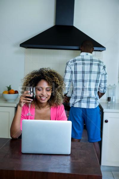 Mujer usando la computadora portátil vino hombre cocina alimentos Foto stock © wavebreak_media