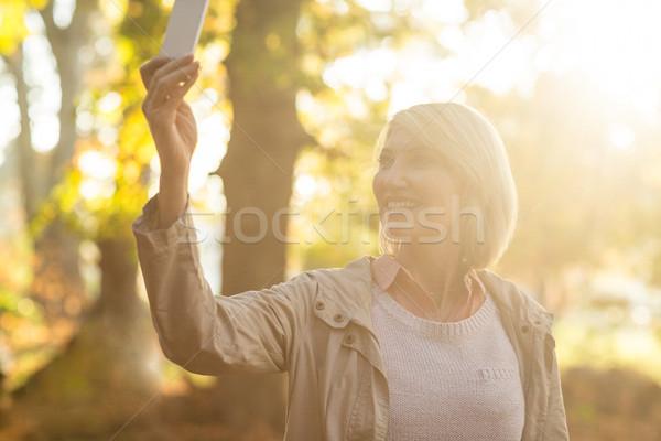Donna matura sorridere telefono cellulare foresta donna Foto d'archivio © wavebreak_media