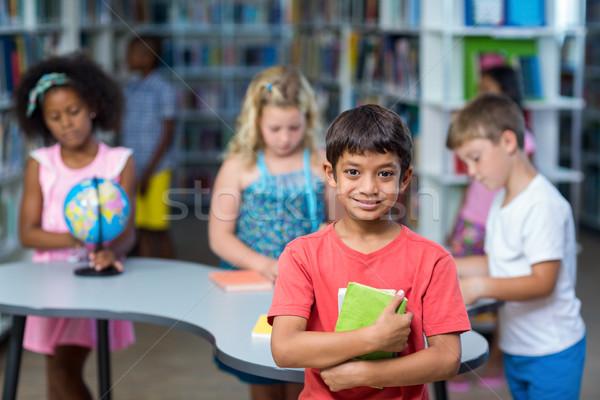 Boy holding books against classmates Stock photo © wavebreak_media