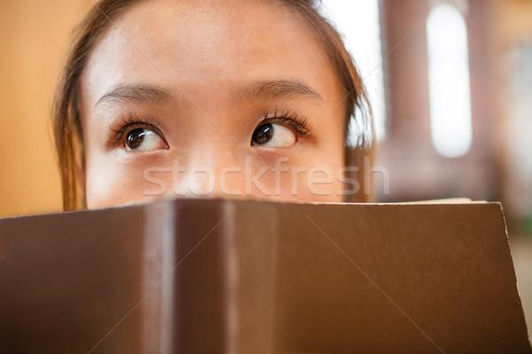 Mulher jovem cobrir cara livro biblioteca Foto stock © wavebreak_media