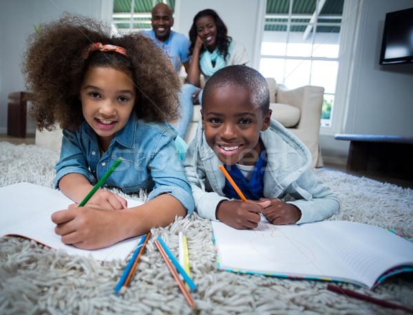 Children doing their homework with parents in background Stock photo © wavebreak_media