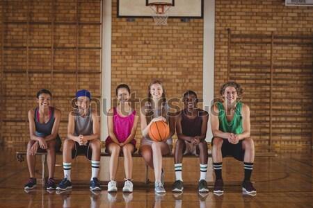 Portrait of high school kids sitting on a bench in basketball court Stock photo © wavebreak_media