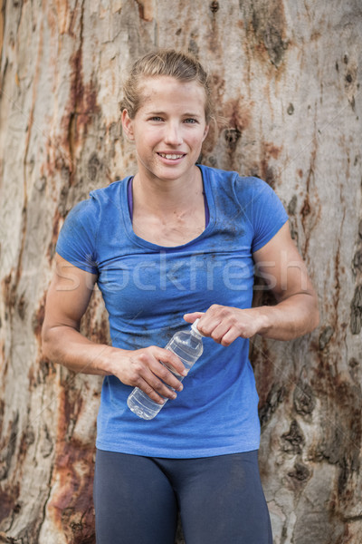 Tired woman holding water bottle during obstacle course Stock photo © wavebreak_media