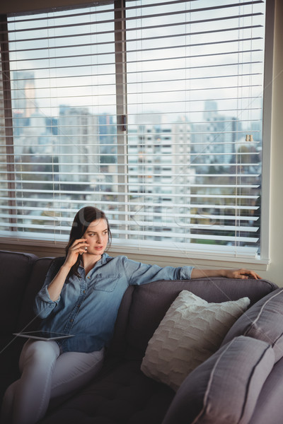 Woman talking on mobile phone while sitting on sofa Stock photo © wavebreak_media