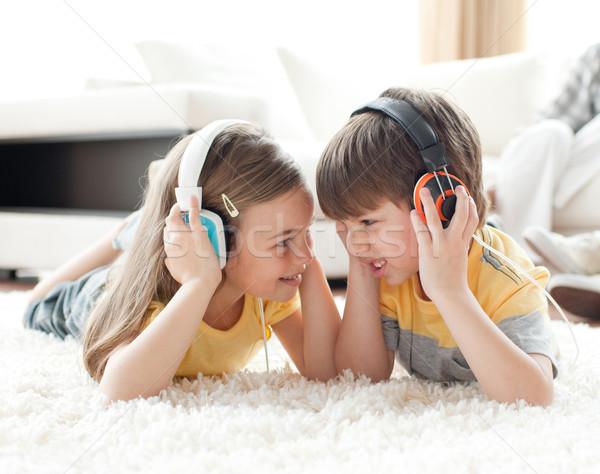 Broers en zussen spelen vloer hoofdtelefoon woonkamer familie Stockfoto © wavebreak_media