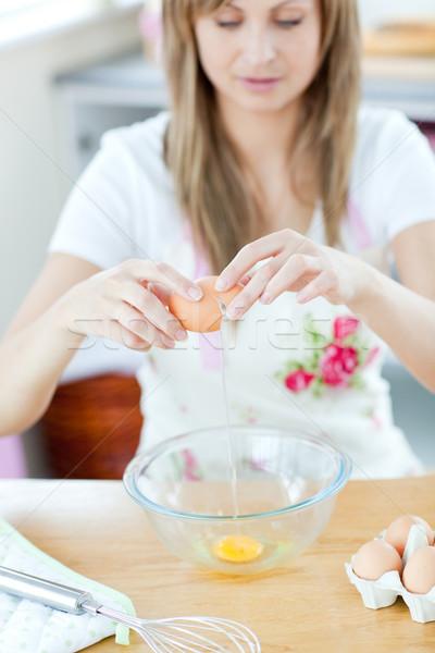 Smiling woman preparing eggs in the kitchen  Stock photo © wavebreak_media