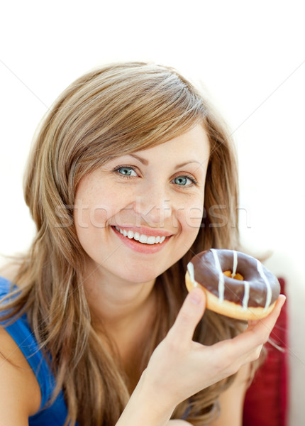 Delighted woman is eating a donut on a sofa  Stock photo © wavebreak_media
