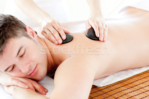 Positive young man enjoying a back massage with hot stone in a healt spa Stock photo © wavebreak_media