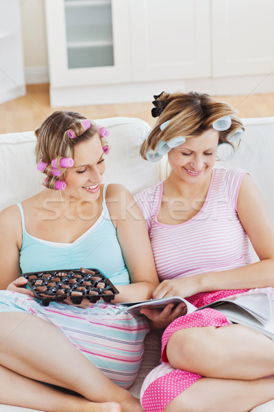 Female friends with hair rollers eating chocolate reading a magazine at home on a sofa Stock photo © wavebreak_media