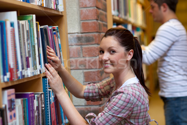 Joyful young woman looking for a book in a bookstore Stock photo © wavebreak_media