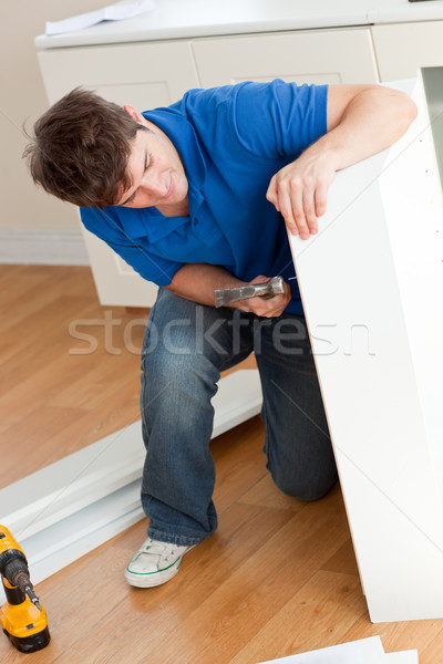 Good-looking man assembling furniture and holding a hammer at home Stock photo © wavebreak_media